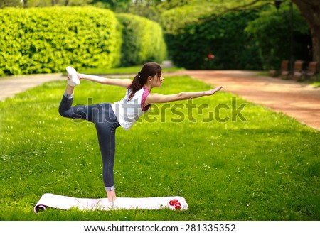 Sportive young woman stretching, doing exercises balancing in yoga pose