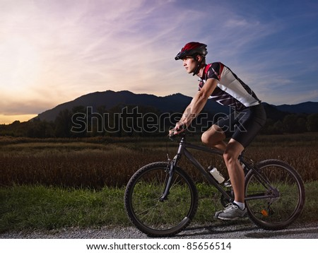 sports activity: young adult cyclist riding fast mountain bike in the countryside. Horizontal shape, side view, full length, copy space - stock photo