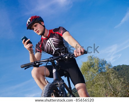 sports activity: young adult cyclist riding mountain bike and text messaging on cellphone. Horizontal shape, low angle view, copy space