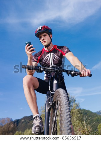 sports activity: young adult cyclist riding mountain bike and text messaging on cellphone. Vertical shape, low angle view