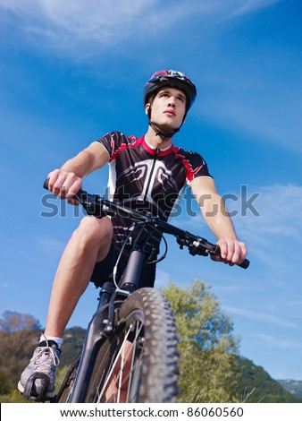sports activity: young adult cyclist riding mountain bike in the countryside. Vertical shape, low angle view, copy space