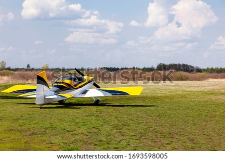 Sports aerobatics, painted in white and yellow , is parked with grass on an open airfield awaiting departure.
