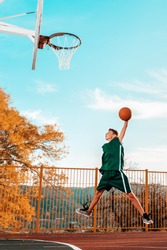Sports and basketball. A young teenager in a green tracksuit jumps and throws a ball into the basket. Blue sky and court in the background. Copy space. Vertical orientation