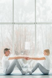 Sports and healthy lifestyle.Sporty middle aged couple sitting on the mat in the white fitness gym and doing stretching while looking each other and smiling. Healthy joints and back. Support trainer.