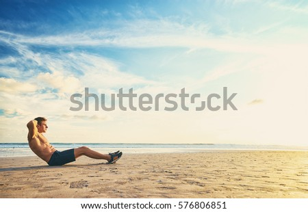 Sports and healthy lifestyle. Young man doing crunches on the ocean beach.