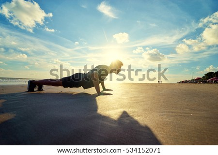 Sports and healthy lifestyle. Young man doing push-ups on the ocean beach.