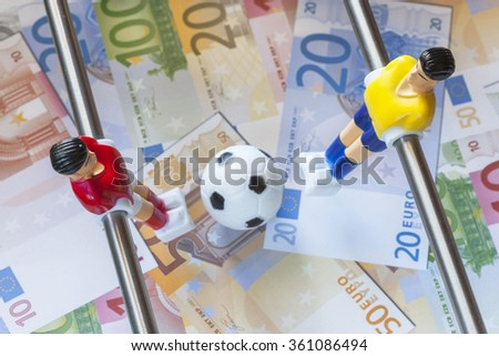 Sports and money. Concept about money spending in football (soccer), sports betting and manipulated fixed matches. Selective focus image