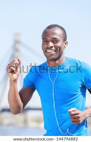 Sports and music. Young african descent men jogging and listening to the MP3 player