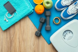 Sports and workout equipment on a wooden floor with healthy snacks, weight loss and physical activity concept