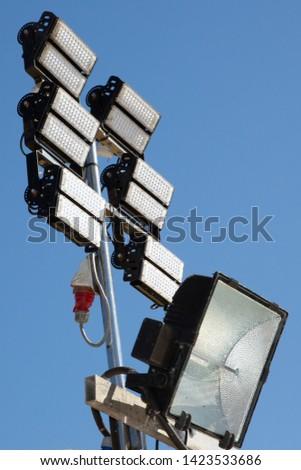 Sports arena floodlights stadium lights against blue day sky background #1423533686