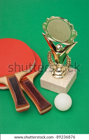 sports awards and  tennis racquets on a green table