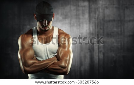 Sports background. Bodybuilding. Strong man  posing on a concrete background