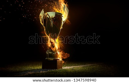 Sports background. Burning trophy goblet. Winner in a competition. Fire and energy. Football field with golden goblet.