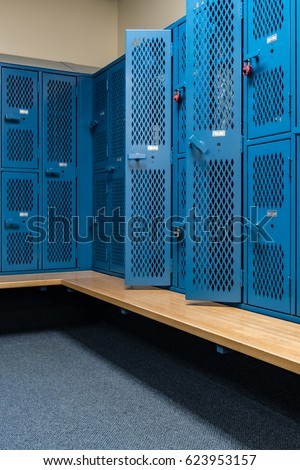 Sports background of a locker room with blue metal cage style lockers, some open, with a wooden bench #623953157