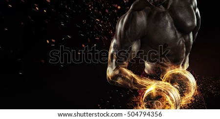 Sports background. Power athletic guy bodybuilder , execute exercise with dumbbells, in dark gym. Fire and energy