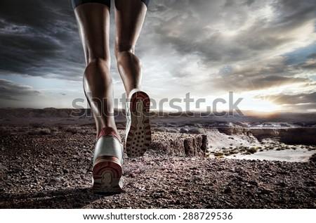 Sports background. Runner feet running on desert closeup on shoe.