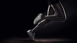Sports background. Runner. Side view of a jogger legs isolated on black