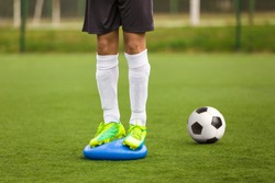 Sports Balance Training. Stability Soccer Training on Balance Cushion. Soccer Skills Session. Players Training on the Field. Grass Football Field. Coaching Soccer Equipment for Field Training