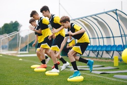 Sports Balance Training. Stability Soccer Training on Balance Cushion. Young Soccer Players Improving Skills. Young Male Athletes Training on the Field. Grass Football Equipment on Practice Field