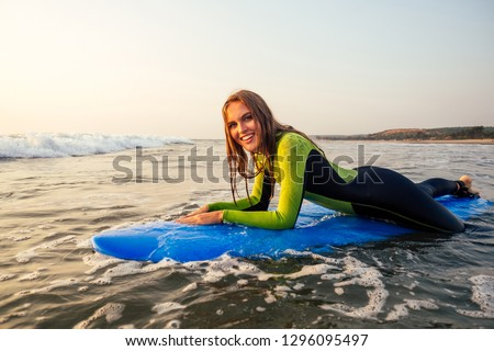 sports beautiful woman in a diving suit lying on a surfboard waiting for a big wave .surf girl in a wetsuit surfing in the ocean at sunset.wet hair, happiness and freedom beach holiday #1296095497