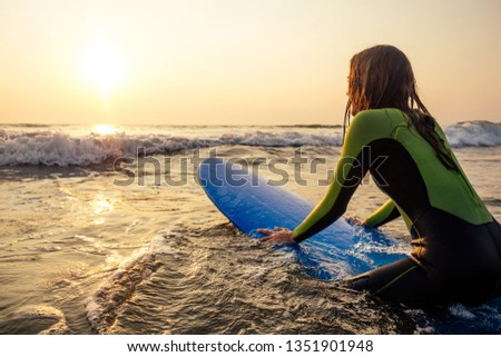 sports beautiful woman in a diving suit lying on a surfboard waiting for a big wave .surf girl in a wetsuit surfing in the ocean at sunset.wet hair, happiness and freedom beach holiday #1351901948