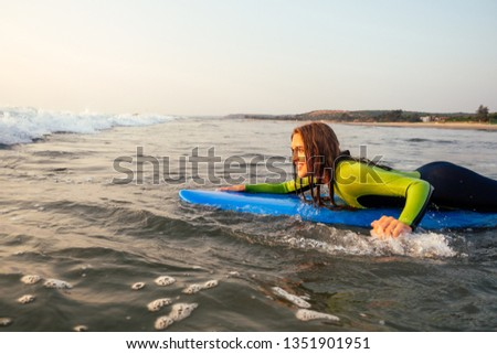 sports beautiful woman in a diving suit lying on a surfboard waiting for a big wave .surf girl in a wetsuit surfing in the ocean at sunset.wet hair, happiness and freedom beach holiday #1351901951