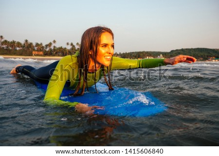 sports beautiful woman in a diving suit lying on a surfboard waiting for a big wave .surf girl in a wetsuit surfing in the ocean at sunset.wet hair, happiness and freedom beach holiday #1415606840
