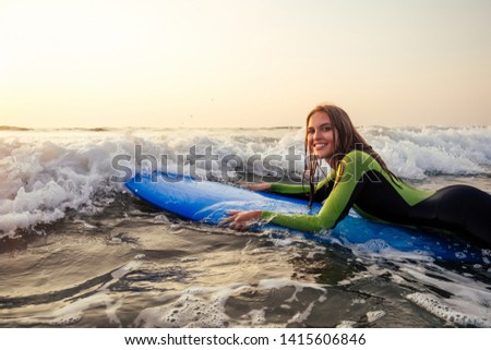 sports beautiful woman in a diving suit lying on a surfboard waiting for a big wave .surf girl in a wetsuit surfing in the ocean at sunset.wet hair, happiness and freedom beach holiday #1415606846