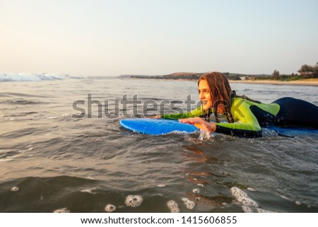 sports beautiful woman in a diving suit lying on a surfboard waiting for a big wave .surf girl in a wetsuit surfing in the ocean at sunset.wet hair, happiness and freedom beach holiday #1415606855