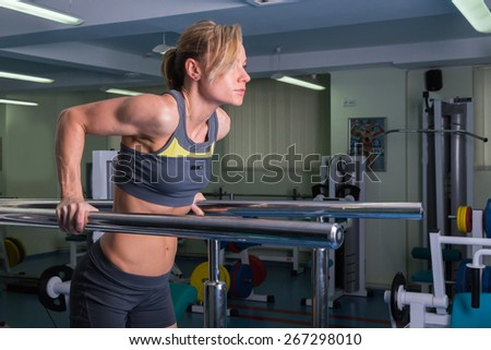 Sports, bodybuilding. Attractive woman in gym.Fitness in the gym. Strength training and beauty. Picture a strong woman. Blonde sexy girl fitness in sexy wear with perfect body posing in the gym.