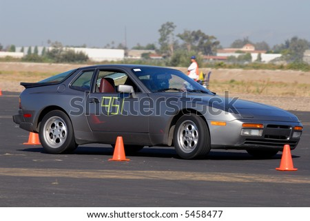 sports car competing turning around cones in autocross race