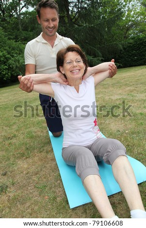 Sports coach training senior woman with stretching exercises