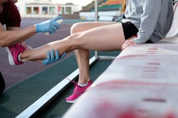 Sports doctor treating injured sportman's knee. Sport medicine in action. Injured tenis player's or athlete leg is anesthetizing by sport doctor using freezing spray.