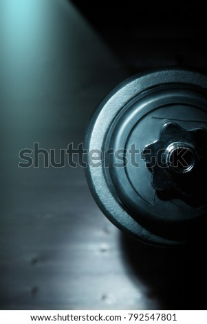 sports dumbbell view in profilesport dumbbell view in profile on a dark background. Space for text