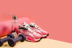 Sports equipment and sneakers on a yellow background. Sport shoes,  yoga mat and dumbbell. Healthy lifestyle. Home  workout.