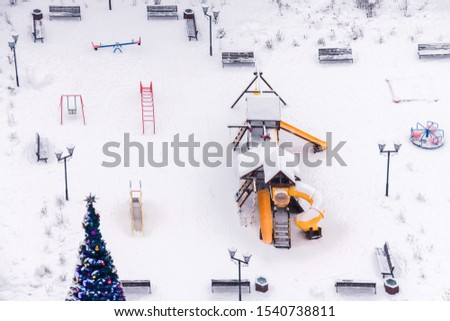 Sports equipment for fitness and benches for rest in the snow winter park workout with decorated New Year tree