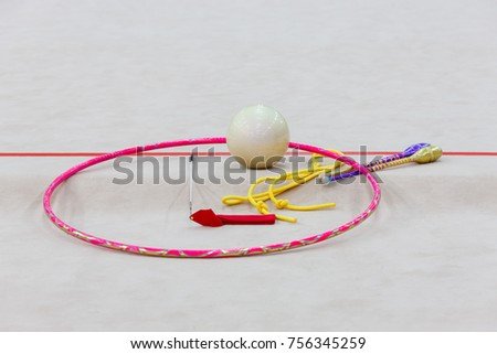 Sports equipment for rhythmic gymnastics lie on the edge of the carpet in the gym. Rhythmic gymnastics clubs, a ball, a tape, a skipping rope, a hoop. Close-up.