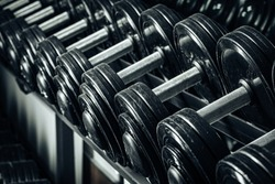 Sports equipment in gym. Dumbbells of different weight close up