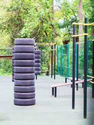 Sports equipment made from car tires on an outdoor sports ground fenced with a green mesh fence