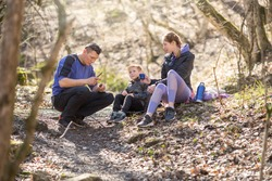 sports family of tourists a man, a woman and a child are sitting resting in the forest on a hike, drinking tea, whittling a stick with a knife