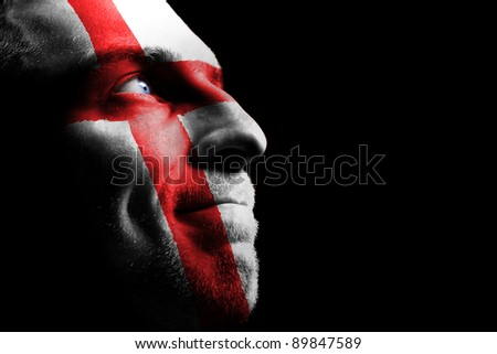 Sports fan - a patriot. On the painted colors of the flag of his country on his face.