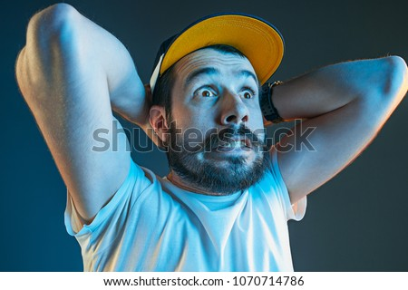 Sports, fan human emotions and people concept - sad young man watching sports on tv and supporting team at home. Crying emotional man screaming in colorful bright lights at studio. Facial expression #1070714786