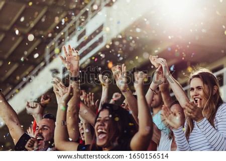 Sports fans clapping hands in stands with falling confetti.  Football team supporters cheering in stadium.