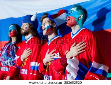 Sports fans singing anthem in stadium