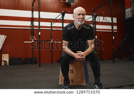 Sports, fitness, age, people, enegry, determination and health concept. Self determined concentrated senior mature male with gray beard and bald head sitting on wooden platform with hands clasped #1289751070