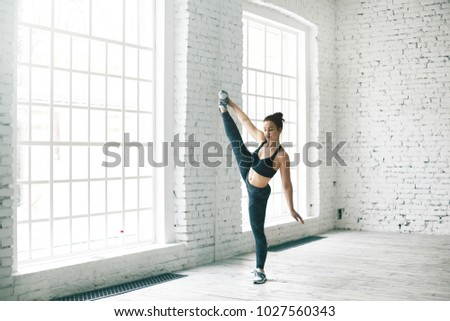 Sports, fitness, flexibility, plasticity and gymnastics concept. Picture of plastic athletic young female dancer stretching legs, doing vertical splits at gym center, warming up before dancing class