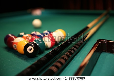 Sports game of billiards on a green cloth. Multi-colored billiard balls in the form of a triangle with numbers, two cues, a cue ball and a triangle on a pool table. Billiards billiard balls close up.