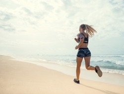 Sports girl running on the beach