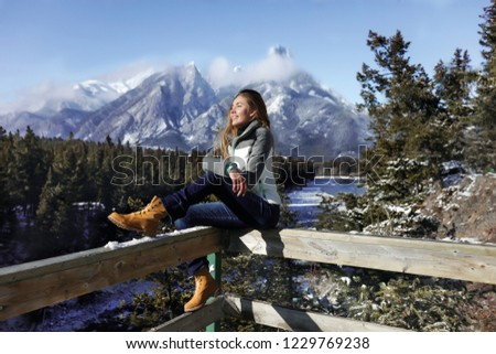 Sports girl sitting on a wooden fence, wearing sportswear, jeans and boots. Cold winter weather in Canada. Sunny day. Mountains and snow on the background.