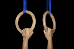 Sports, gymnastics: Two male hands grab traditional wooden gymnastic rings tightly in a gym isolated on black background - concept athlete athletics olympics olympic games strength health activity